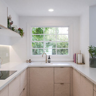 Photo of a medium sized modern u-shaped kitchen/diner in London with a built-in sink, flat-panel cabinets, light wood cabinets, composite countertops, green splashback, ceramic splashback, stainless steel appliances, vinyl flooring, a breakfast bar, grey floors and white worktops.