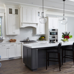 Large farmhouse eat-in kitchen remodeling - Eat-in kitchen - large farmhouse l-shaped dark wood floor eat-in kitchen idea in Wilmington with raised-panel cabinets, white cabinets, granite countertops, white backsplash, subway tile backsplash, stainless steel appliances and an island