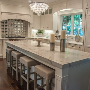 Large traditional enclosed kitchen designs - Large elegant l-shaped dark wood floor and brown floor enclosed kitchen photo in Boston with a farmhouse sink, shaker cabinets, white cabinets, marble countertops, white backsplash, mirror backsplash, paneled appliances and an island