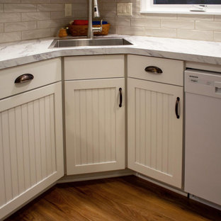 Photo of a small transitional l-shaped eat-in kitchen in Cleveland with an undermount sink, recessed-panel cabinets, white cabinets, laminate benchtops, beige splashback, porcelain splashback, white appliances, vinyl floors, no island, brown floor and white benchtop.