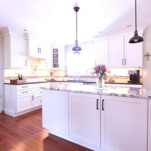 Mittelgroße Klassische Wohnküche in U-Form mit Unterbauwaschbecken, Schrankfronten mit vertiefter Füllung, weißen Schränken, Granit-Arbeitsplatte, Küchenrückwand in Beige, Rückwand aus Travertin, Küchengeräten aus Edelstahl, braunem Holzboden, Kücheninsel, braunem Boden und beiger Arbeitsplatte in Sonstige
