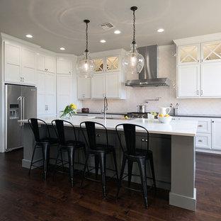 Modelo de cocina en L, clásica renovada, con fregadero bajoencimera, armarios estilo shaker, puertas de armario blancas, salpicadero blanco, suelo de madera oscura y una isla