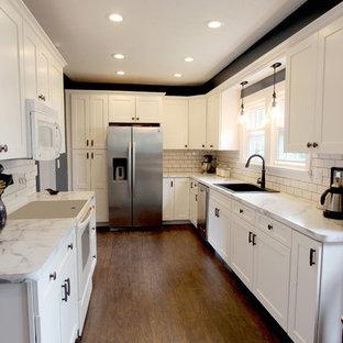 クリーブランドの中くらいのトランジショナルスタイルのおしゃれなキッチン (アンダーカウンターシンク、フラットパネル扉のキャビネット、白いキャビネット、ラミネートカウンター、白いキッチンパネル、セラミックタイルのキッチンパネル、白い調理設備、リノリウムの床、アイランドなし) の写真