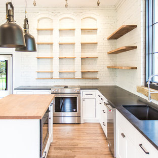 This is an example of a medium sized classic l-shaped kitchen/diner in Other with a submerged sink, shaker cabinets, white cabinets, granite worktops, white splashback, brick splashback, stainless steel appliances, light hardwood flooring, an island, red floors and black worktops.