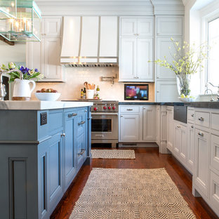 Traditional l-shaped eat-in kitchen in St Louis with a farmhouse sink, recessed-panel cabinets, white cabinets, white splashback, subway tile splashback, stainless steel appliances, dark hardwood floors, with island and soapstone benchtops.