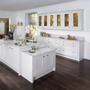 Foto di una grande cucina lineare contemporanea con lavello sottopiano, ante con riquadro incassato, ante bianche, top in vetro riciclato, paraspruzzi bianco, parquet scuro e isola