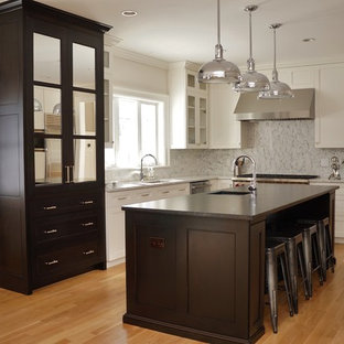 Mid-sized industrial eat-in kitchen inspiration - Inspiration for a mid-sized industrial l-shaped light wood floor and brown floor eat-in kitchen remodel in Boston with an undermount sink, gray backsplash, stainless steel appliances, an island, shaker cabinets, white cabinets, laminate countertops, subway tile backsplash and brown countertops