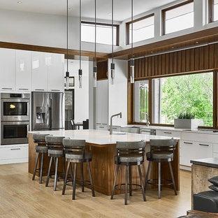 Esempio di una grande cucina design con ante lisce, ante bianche, top in quarzo composito, elettrodomestici in acciaio inossidabile, parquet chiaro, un'isola, pavimento beige, lavello stile country, paraspruzzi a finestra e top bianco