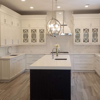 Inspiration for a mid-sized transitional u-shaped medium tone wood floor eat-in kitchen remodel in New York with an undermount sink, shaker cabinets, white cabinets, solid surface countertops, white backsplash, stone slab backsplash, stainless steel appliances and an island