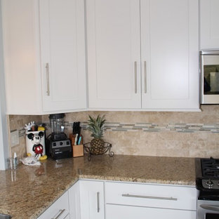 Small traditional eat-in kitchen ideas - Small elegant l-shaped travertine floor eat-in kitchen photo in Philadelphia with white cabinets, an undermount sink, shaker cabinets, granite countertops, beige backsplash, porcelain backsplash, stainless steel appliances and an island