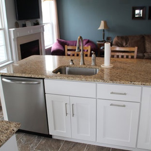 Small traditional eat-in kitchen photos - Inspiration for a small timeless l-shaped travertine floor eat-in kitchen remodel in Philadelphia with an undermount sink, shaker cabinets, white cabinets, granite countertops, beige backsplash, porcelain backsplash, stainless steel appliances and an island
