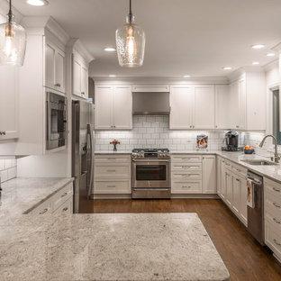 Foto på ett mellanstort gul kök, med en nedsänkt diskho, luckor med infälld panel, vita skåp, granitbänkskiva, vitt stänkskydd, stänkskydd i tunnelbanekakel, rostfria vitvaror, mellanmörkt trägolv, en halv köksö och brunt golv