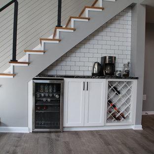 デトロイトの中サイズのビーチスタイルのおしゃれなキッチン (エプロンフロントシンク、シェーカースタイル扉のキャビネット、白いキャビネット、御影石カウンター、白いキッチンパネル、セラミックタイルのキッチンパネル、シルバーの調理設備の、クッションフロア、グレーの床、黒いキッチンカウンター) の写真