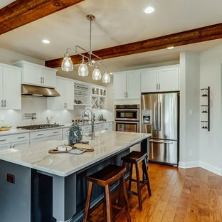 Mid-sized contemporary open concept kitchen ideas - Open concept kitchen - mid-sized contemporary l-shaped medium tone wood floor and brown floor open concept kitchen idea in Richmond with a farmhouse sink, shaker cabinets, white cabinets, quartzite countertops, white backsplash, subway tile backsplash, stainless steel appliances and an island