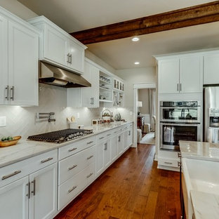 Mid-sized contemporary open concept kitchen remodeling - Example of a mid-sized trendy l-shaped medium tone wood floor and brown floor open concept kitchen design in Richmond with a farmhouse sink, shaker cabinets, white cabinets, quartzite countertops, white backsplash, subway tile backsplash, stainless steel appliances and an island