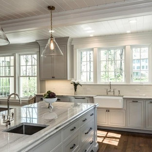Farmhouse kitchen pictures - Cottage medium tone wood floor kitchen photo in Boston with a farmhouse sink, raised-panel cabinets, gray cabinets, quartzite countertops, white backsplash, porcelain backsplash, stainless steel appliances and an island