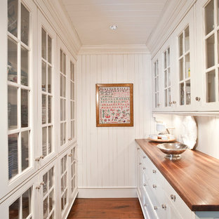 Elegant kitchen pantry photo in Indianapolis with wood countertops, glass-front cabinets and white cabinets