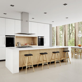 This is an example of a mid-sized scandinavian galley eat-in kitchen in Sydney with a drop-in sink, white cabinets, quartz benchtops, stainless steel appliances, porcelain floors and with island.