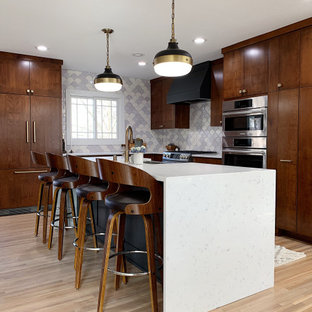 Design ideas for a large midcentury l-shaped open plan kitchen in Minneapolis with a drop-in sink, flat-panel cabinets, dark wood cabinets, onyx benchtops, white splashback, ceramic splashback, stainless steel appliances, dark hardwood floors, with island, brown floor and white benchtop.