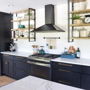他の地域の広いカントリー風おしゃれなキッチン (アンダーカウンターシンク、シェーカースタイル扉のキャビネット、黒いキャビネット、珪岩カウンター、白いキッチンパネル、塗装板のキッチンパネル、シルバーの調理設備、淡色無垢フローリング、ベージュの床、白いキッチンカウンター) の写真