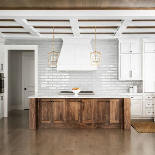This is an example of a large country u-shaped kitchen in Chicago with an undermount sink, shaker cabinets, white cabinets, quartz benchtops, grey splashback, subway tile splashback, stainless steel appliances, light hardwood floors, with island, brown floor, white benchtop and coffered.