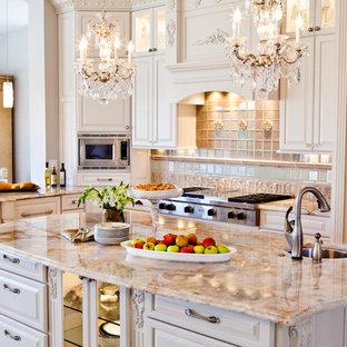 На фото: большие п-образные кухни в классическом стиле с обеденным столом, тройной раковиной, фасадами с выступающей филенкой, белыми фасадами, гранитной столешницей, бежевым фартуком, фартуком из каменной плитки, техникой под мебельный фасад, полом из травертина и островом