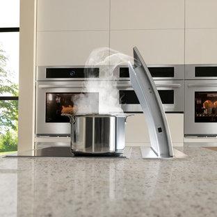 Moderne Wohnküche mit flächenbündigen Schrankfronten, Arbeitsplatte aus Recyclingglas und Küchengeräten aus Edelstahl in New York