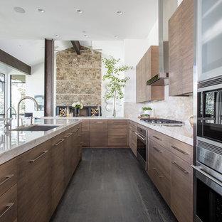 Diseño de cocina en U, actual, abierta, con fregadero bajoencimera, armarios con paneles lisos, puertas de armario de madera oscura, salpicadero beige, electrodomésticos de acero inoxidable, suelo de madera oscura y una isla
