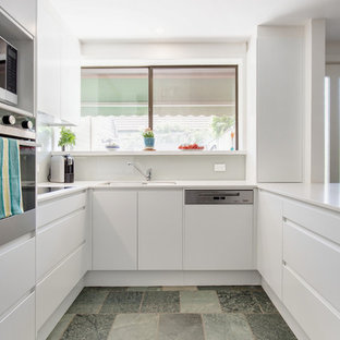 Moderne Küche in U-Form mit Unterbauwaschbecken, flächenbündigen Schrankfronten, weißen Schränken, Küchenrückwand in Weiß, Küchengeräten aus Edelstahl, Halbinsel, blauem Boden und weißer Arbeitsplatte in Sydney