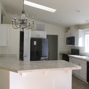 Inspiration for a mid-sized traditional l-shaped eat-in kitchen in Hawaii with a double-bowl sink, beaded inset cabinets, white cabinets, laminate benchtops, beige splashback, ceramic splashback, black appliances, vinyl floors and a peninsula.