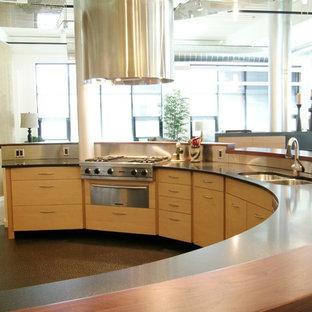 Esempio di una grande cucina moderna con lavello a doppia vasca, ante lisce, ante in legno chiaro, top in quarzo composito, paraspruzzi verde, elettrodomestici in acciaio inossidabile, pavimento in cemento, isola, paraspruzzi con piastrelle di metallo e pavimento marrone
