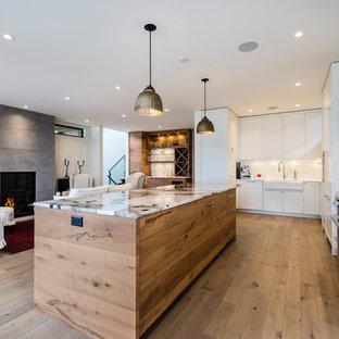 バンクーバーの広いコンテンポラリースタイルのおしゃれなキッチン (シェーカースタイル扉のキャビネット、白いキャビネット、大理石カウンター、無垢フローリング、緑の床、ターコイズのキッチンカウンター) の写真