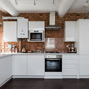 This is an example of a contemporary l-shaped kitchen in London with a built-in sink, flat-panel cabinets, white cabinets, red splashback, brick splashback, integrated appliances, dark hardwood flooring, no island, brown floors and grey worktops.