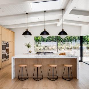 Bild på ett retro vit vitt kök, med marmorbänkskiva, flera köksöar, släta luckor, skåp i ljust trä, integrerade vitvaror, ljust trägolv och beiget golv