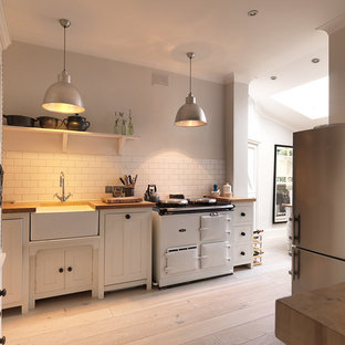 Example of a mid-sized danish light wood floor and beige floor kitchen design in London with a farmhouse sink, shaker cabinets, white cabinets, white backsplash, subway tile backsplash, stainless steel appliances and no island