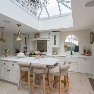This is an example of a large traditional l-shaped eat-in kitchen in Hertfordshire with a single-bowl sink, shaker cabinets, yellow cabinets, soapstone benchtops, metallic splashback, mirror splashback, stainless steel appliances, porcelain floors, with island, beige floor and white benchtop.