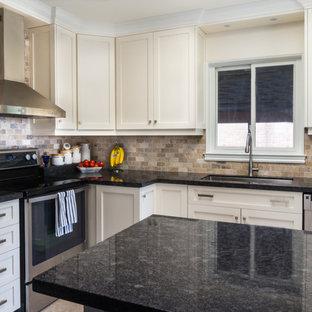 トロントの中くらいのトランジショナルスタイルのおしゃれなキッチン (アンダーカウンターシンク、シェーカースタイル扉のキャビネット、白いキャビネット、御影石カウンター、ベージュキッチンパネル、シルバーの調理設備、セラミックタイルの床、レンガのキッチンパネル) の写真