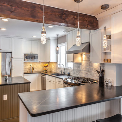Eat-in kitchen - mid-sized craftsman u-shaped light wood floor eat-in kitchen idea in Burlington with an undermount sink, shaker cabinets, white cabinets, soapstone countertops, white backsplash, stone tile backsplash, stainless steel appliances and an island