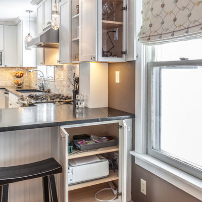 Example of a mid-sized arts and crafts u-shaped light wood floor eat-in kitchen design in Burlington with an undermount sink, shaker cabinets, white cabinets, soapstone countertops, white backsplash, stone tile backsplash, stainless steel appliances and an island