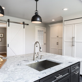 Large rural kitchen pantry in New York with a submerged sink, recessed-panel cabinets, white cabinets, granite worktops, white splashback, porcelain splashback, integrated appliances, porcelain flooring and an island.