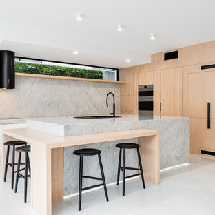 This is an example of a large modern l-shaped kitchen pantry in Brisbane with an undermount sink, beaded inset cabinets, light wood cabinets, marble benchtops, white splashback, marble splashback, black appliances, marble floors, with island, white floor and white benchtop.
