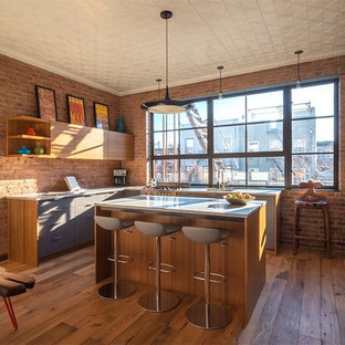 Large industrial eat-in kitchen designs - Example of a large urban l-shaped medium tone wood floor eat-in kitchen design in New York with a single-bowl sink, flat-panel cabinets, medium tone wood cabinets, window backsplash and an island