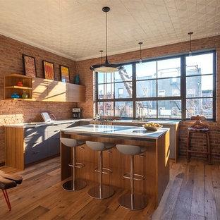 Große Industrial Wohnküche in L-Form mit Waschbecken, flächenbündigen Schrankfronten, hellbraunen Holzschränken, Rückwand-Fenster, braunem Holzboden und Kücheninsel in New York