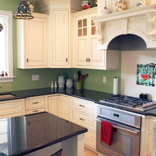 Photo of a large traditional u-shaped eat-in kitchen in New York with an undermount sink, beaded inset cabinets, white cabinets, granite benchtops, white splashback, ceramic splashback, stainless steel appliances, ceramic floors and with island.