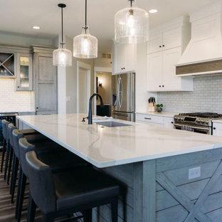 Inspiration för ett stort lantligt vit vitt kök, med en undermonterad diskho, skåp i shakerstil, vita skåp, bänkskiva i kvarts, vitt stänkskydd, rostfria vitvaror, vinylgolv, en köksö, brunt golv och stänkskydd i tunnelbanekakel