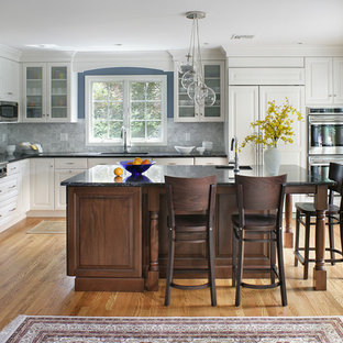 Example of a large transitional l-shaped light wood floor and brown floor enclosed kitchen design in New York with raised-panel cabinets, white cabinets, stainless steel appliances, an undermount sink, granite countertops, gray backsplash, marble backsplash and an island