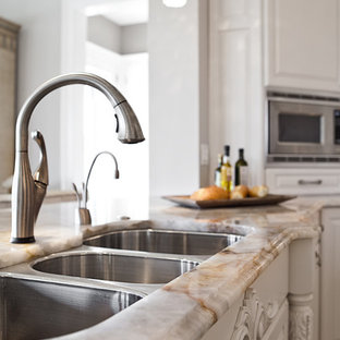 Large traditional u-shaped kitchen/diner in St Louis with a triple-bowl sink, raised-panel cabinets, white cabinets, granite worktops, beige splashback, stone tiled splashback, integrated appliances, travertine flooring and an island.