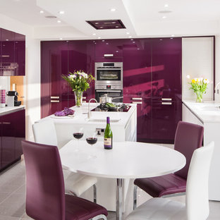 This is an example of a modern kitchen in Kent with flat-panel cabinets, white cabinets, panelled appliances, porcelain floors and with island.