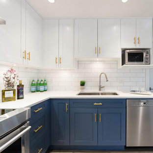 Design ideas for a mid-sized country eat-in kitchen in Vancouver with a double-bowl sink, recessed-panel cabinets, blue cabinets, solid surface benchtops, white splashback, subway tile splashback, stainless steel appliances, vinyl floors and with island.
