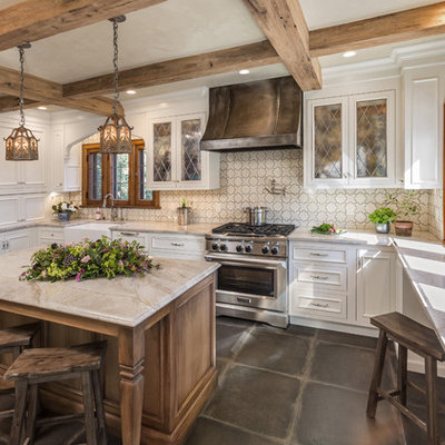 Enclosed kitchen - mid-sized traditional u-shaped gray floor and porcelain tile enclosed kitchen idea in Milwaukee with a farmhouse sink, recessed-panel cabinets, white cabinets, an island, marble countertops, white backsplash, cement tile backsplash, paneled appliances and multicolored countertops